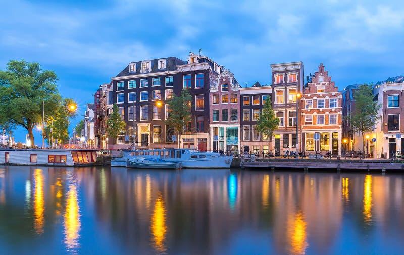 Opini?o da cidade da noite do canal de Amsterd?o, de casas holandesas t?picas e de barcos, Holanda, Pa?ses Baixos fotos de stock royalty free