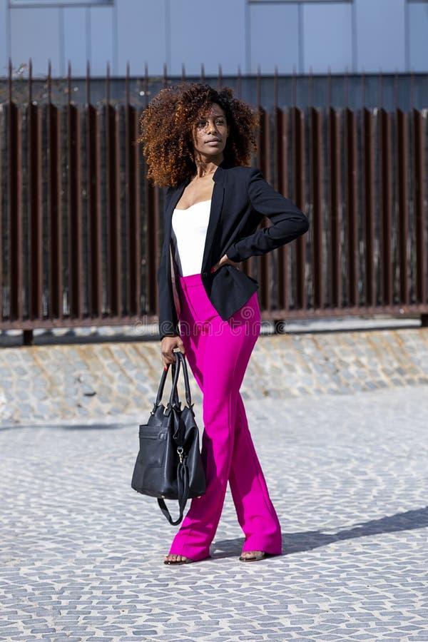 Opini?o dianteira a mulher encaracolado bonita nova que veste a roupa e a bolsa elegantes ao estar na rua no dia ensolarado imagens de stock