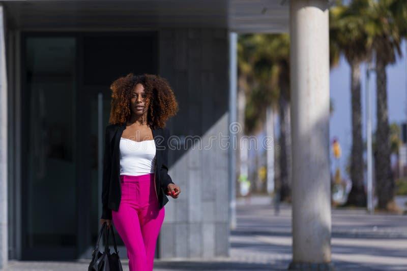 Opini?o dianteira a mulher encaracolado bonita nova que veste a roupa e a bolsa elegantes ao estar na rua no dia ensolarado fotos de stock