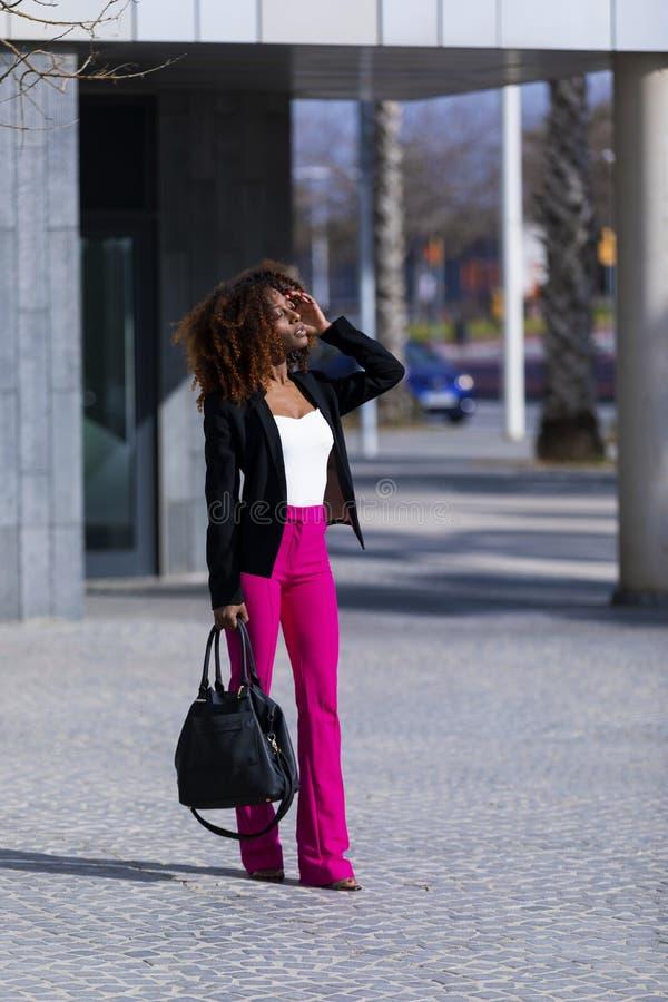 Opini?o dianteira a mulher encaracolado bonita nova que veste a roupa e a bolsa elegantes ao estar na rua no dia ensolarado imagem de stock royalty free