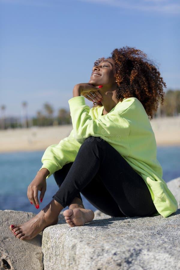 Opini?o lateral a mulher afro encaracolado bonita que senta-se nas rochas do quebra-mar que riem ao descansar a m?o sob os olhos  fotos de stock