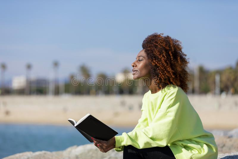 Opini?o lateral a mulher afro encaracolado nova que senta-se em um quebra-mar que guarda um livro ao sorrir e ao olhar afastado f fotografia de stock royalty free