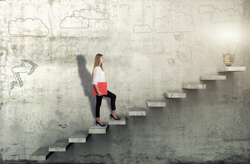 Opini?o lateral a mulher de neg?cios nova que escala as escadas com a l?mpada da ideia no fundo concreto imagens de stock royalty free