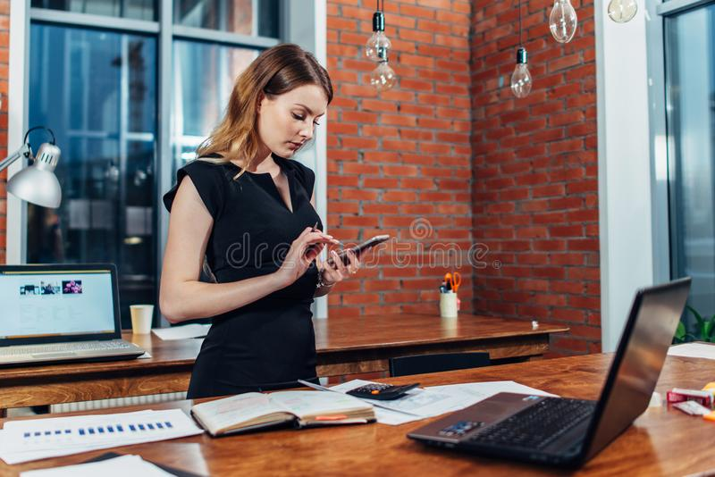 Opini?o superior a mulher que trabalha usando o smartphone que est? em seu local de trabalho no escrit?rio criativo foto de stock