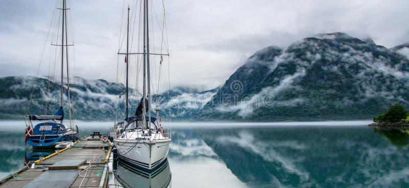 Opini?o surpreendente da paisagem da natureza do lago cercada por montanhas nevoentas Embarca??es ou navios de naviga??o Lago nat fotos de stock royalty free