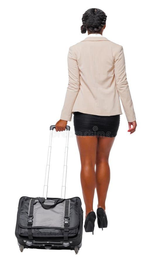 Opini?o traseira o afro-americano preto no vestu?rio formal que anda com uma mala de viagem imagens de stock royalty free