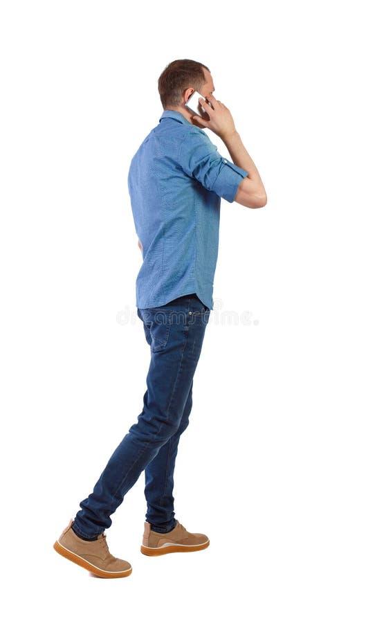 Opini?o traseira o homem que anda com um telefone celular fotografia de stock