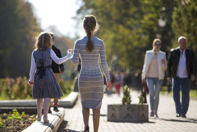 Opini?o traseira a menina e a m?e da crian?a nos vestidos unidas que mant?m as m?os no ar livre morno do dia no fundo ensolarado imagem de stock