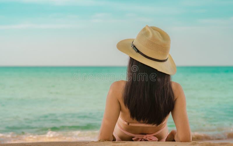 Opini?o traseira a mulher asi?tica nova feliz no chap?u cor-de-rosa do roupa de banho e de palha para relaxar e apreciar o feriad imagens de stock royalty free
