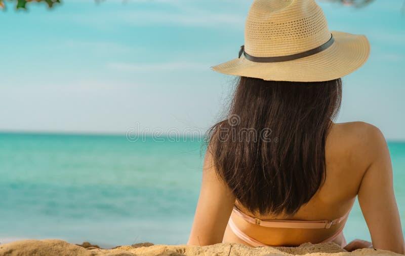 Opini?o traseira a mulher asi?tica nova feliz no chap?u cor-de-rosa do roupa de banho e de palha para relaxar e apreciar o feriad fotografia de stock royalty free