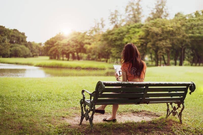 Opini?o traseira a mulher feliz da beleza em equipamentos ocasionais usando a tabuleta no fundo do parque nacional Estilos de vid fotografia de stock royalty free