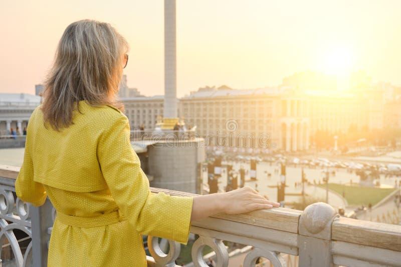 Opini?o traseira a mulher que olha o panorama de nivelar a cidade F?mea adulta na capa de chuva amarela exterior, espa?o da c?pia fotos de stock