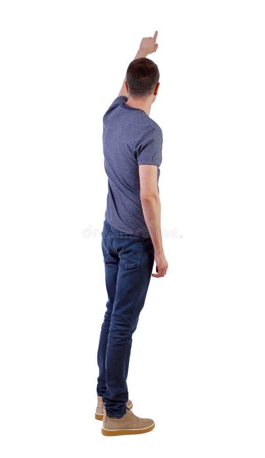 Opini?o traseira um homem em pontos das cal?as de brim sua m?o para cima imagens de stock