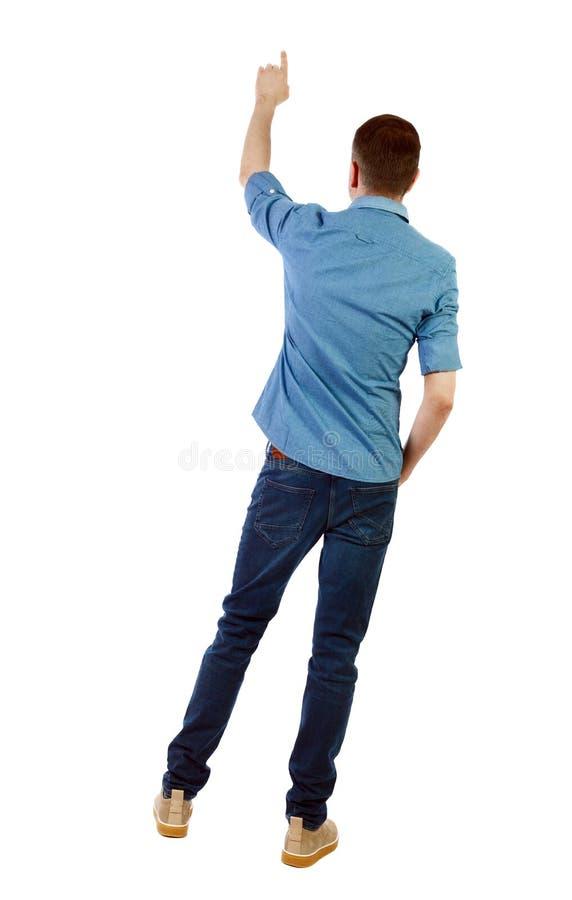 Opini?o traseira um homem em pontos das cal?as de brim sua m?o para cima imagens de stock royalty free