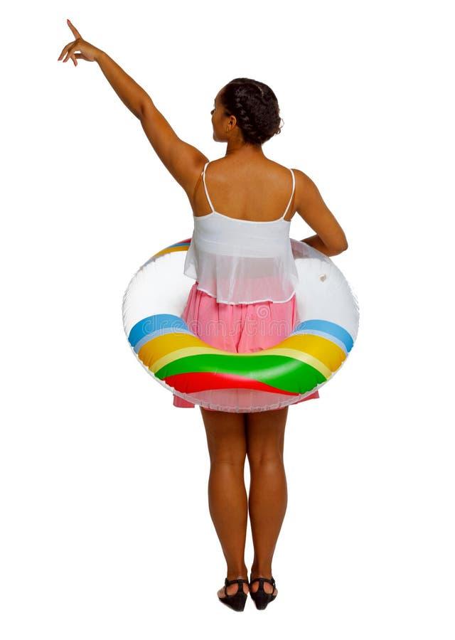 Opini?o traseira uma mulher afro-americana com um c?rculo infl?vel que aponte a m?o acima fotos de stock