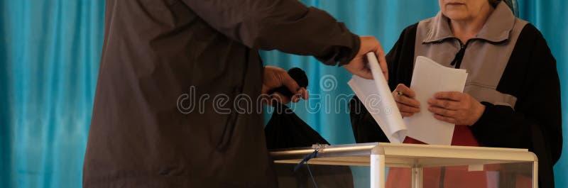 Opiniepeilingspost Nationale stemming, verkiezingen Bejaarde en vrouw in onderdompelende stemmingen in burger in een transparante royalty-vrije stock foto