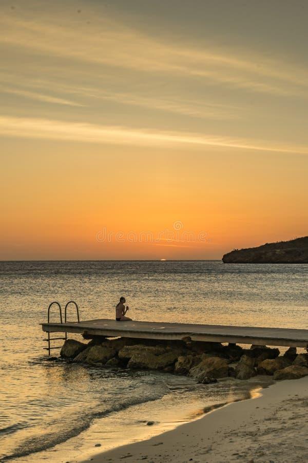 Opiniones de Curaçao de la playa de la puesta del sol del embarcadero de PortoMari fotos de archivo libres de regalías