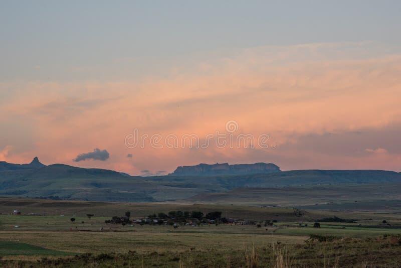 Opiniones de la puesta del sol de las montañas de Drakensberg que rodean el Amphitheatre foto de archivo