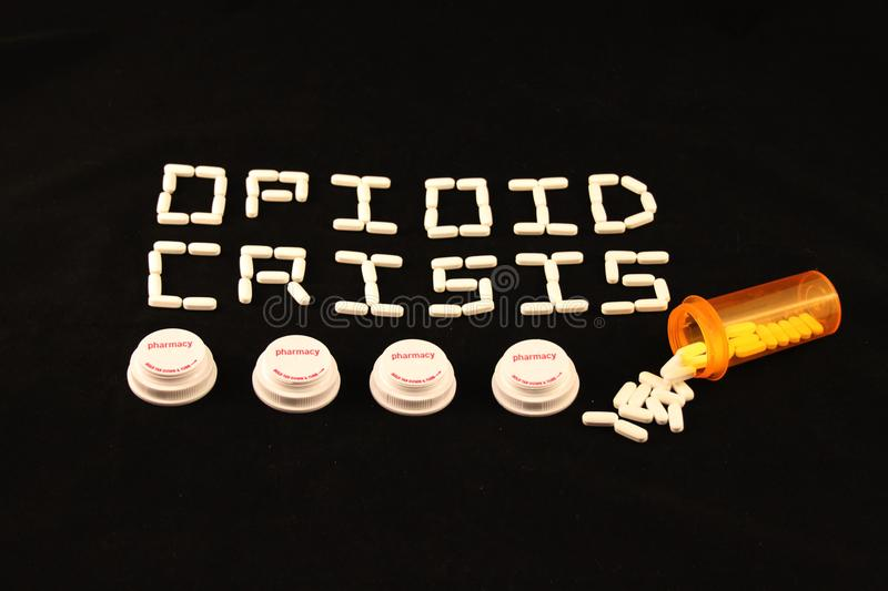 Opioid crisis spelled out with white pills above several prescription bottle lids on a black background stock image