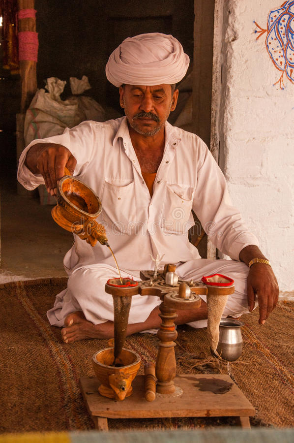 Opium water ritual at Bishnoi. Offering opium water is the village's traditional way of greeting guests. The man takes a small ball of dry opium and smashes it royalty free stock photo