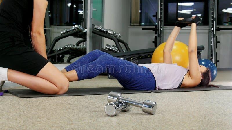 Opleiding Een jonge vrouw die haar abs pompen Haar trainer zit op haar benen royalty-vrije stock afbeelding