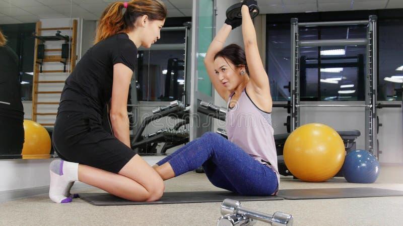 Opleiding Een jonge vrouw met beenprothese die haar abs pompen Haar trainer zit op haar benen stock fotografie