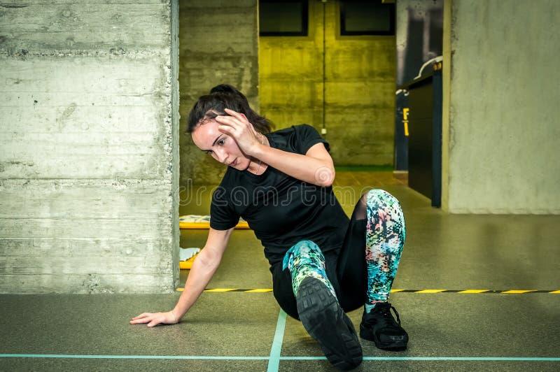 Opleiding van jong mooi en aantrekkelijk meisje voor sterkte en conditionerende training in de gymnastiek stock foto's