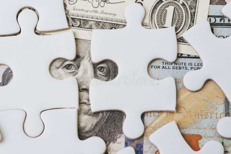 Oplossend het financiële of bedrijfsprobleem of het idee voor het maken van geldconcept, wit puzzelspel op Amerikaanse dollarbank royalty-vrije stock afbeeldingen