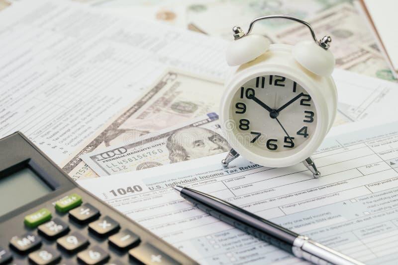 Opodatkowywa czas w Kwietnia pojęciu, pióro na 1040 USA podatku dochodowego plombowania indywidualnej formie z budzikiem i dolaró obrazy stock