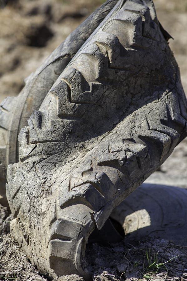 Opony gumy zanieczyszczenie Stara szpotawa ciągnikowa opona pozuje zagrożenie zdjęcie royalty free
