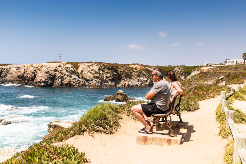 Oporto Covo, Portugal - un par se sienta en un banco mientras que admiting la visión desde arriba de la playa del DOS Buizinhos d imagen de archivo