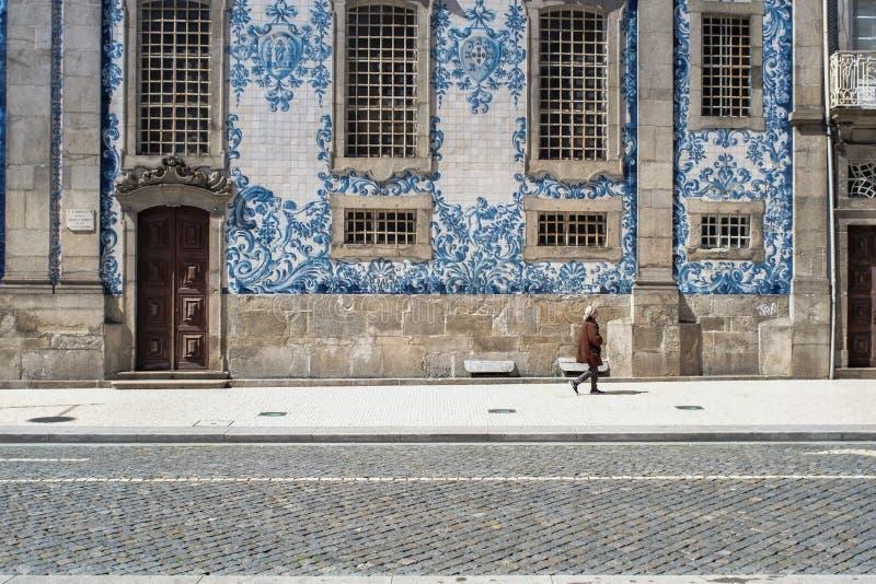 Oporto, Portogallo - 4 aprile 2017: La donna che cammina davanti ad una facciata piastrellata di Igreja fa Carmo nella P fotografia stock libera da diritti