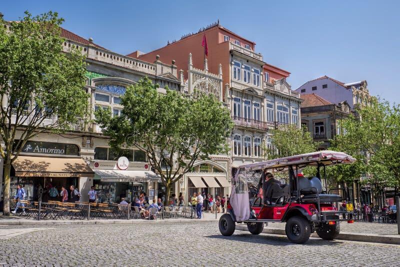 OPORTO, PORTOGALLO - 25 APRILE 2018: Tuk-tuk sulla via con la biblioteca e la libreria famose Livraria Lello a Oporto immagini stock