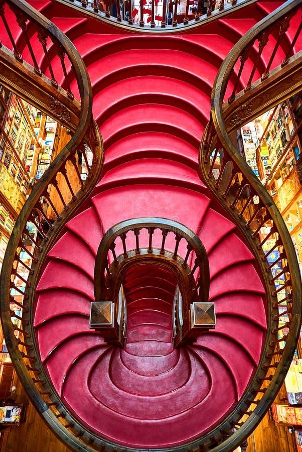 OPORTO, PORTUGAL - 11 de diciembre de 2018: Escalera de madera grande con pasos rojos dentro de la librería Livraria Lello de la  imagen de archivo libre de regalías