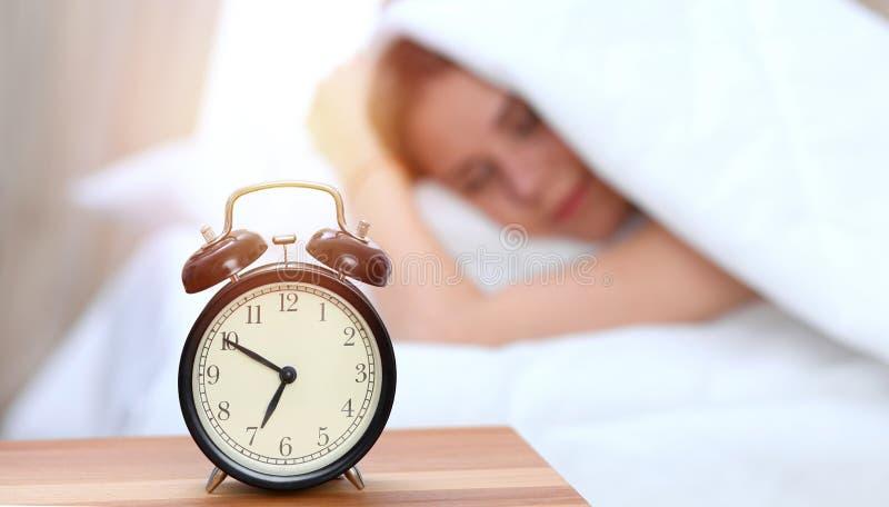 Oposto do despertador da jovem mulher sonolento Acorde cedo, não obtendo a bastante o conceito do sono imagem de stock