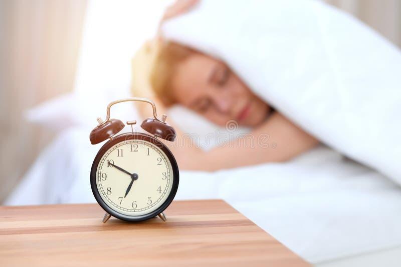 Oposto do despertador da jovem mulher sonolento Acorde cedo, não obtendo a bastante o conceito do sono imagens de stock