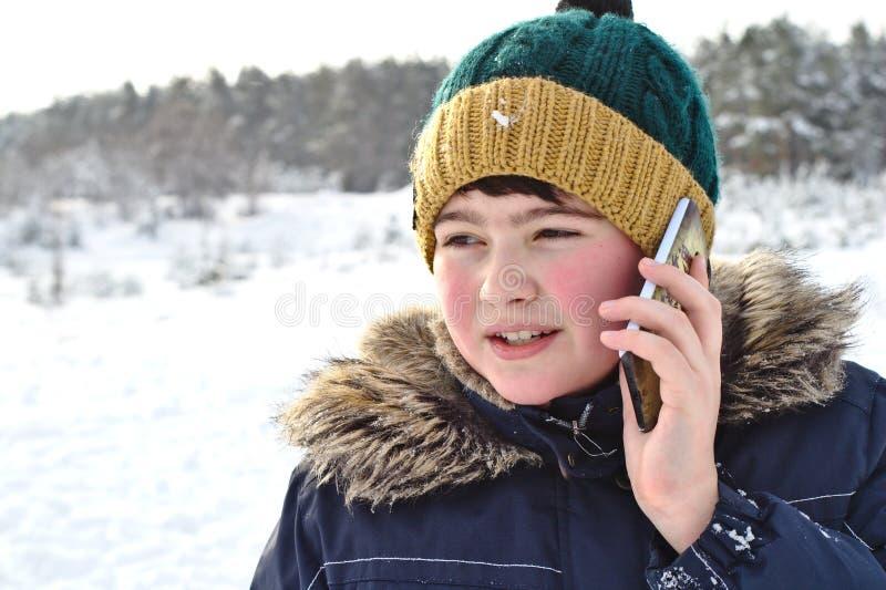opowiadać na telefon chłopiec w trykotowym kapeluszu z futerkowym kapiszonem na zima spacerze i dymienicą fotografia royalty free