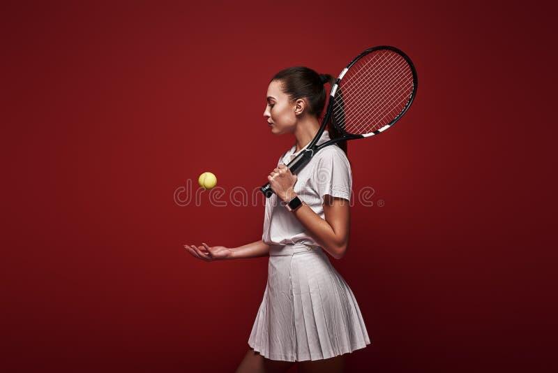 Opowiada z twój raquet, sztuka z twój sercem Młoda gracz w tenisa pozycja odizolowywająca nad czerwonym tłem z kantem i obrazy royalty free