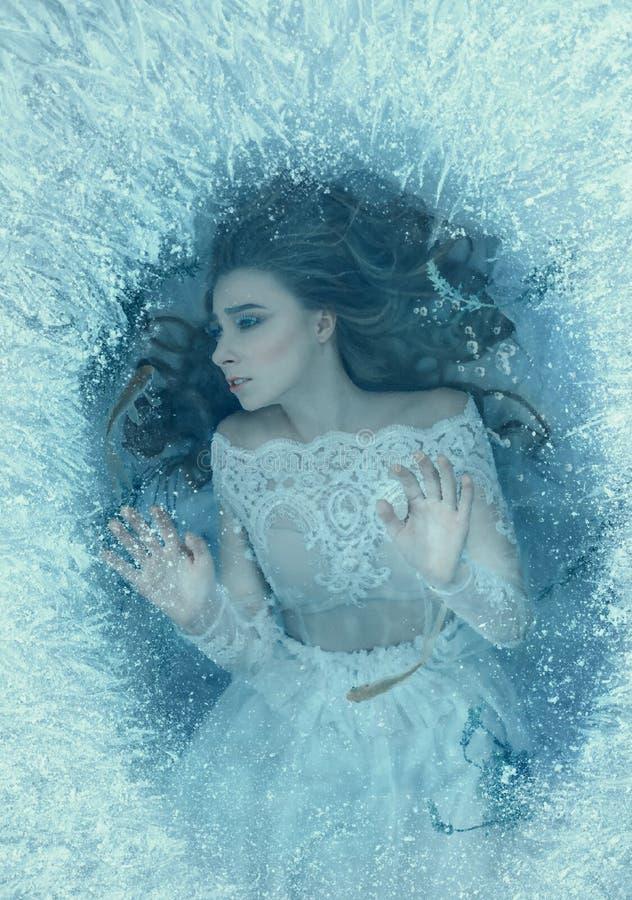 Opowieść sypialny piękno Dziewczyna budził się up przy dnem zamarznięty jeziora, ryba i gałęzatki pływanie, wokoło ona strzyżenie obraz stock