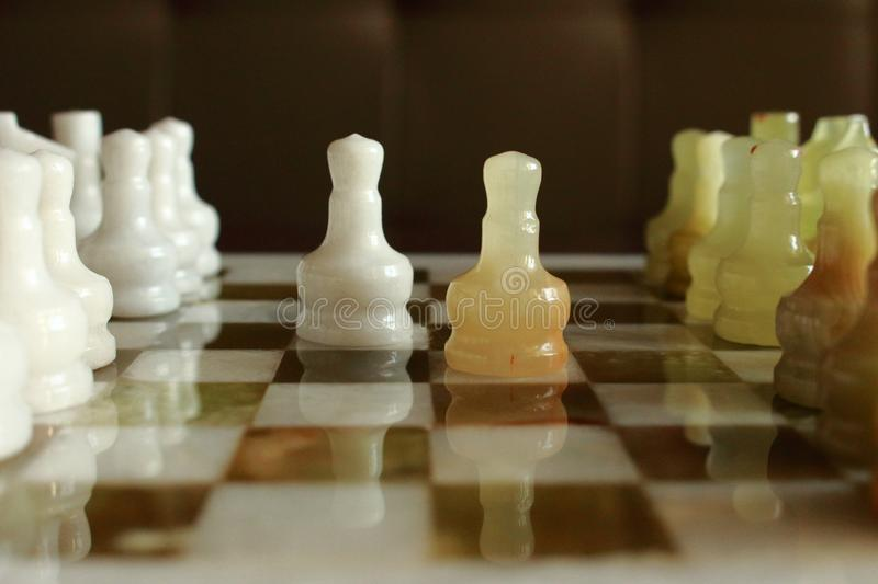 Opponent pawns in front of each other on marble chessboard as challenge and intelligant fight concept. First steps of chess game. royalty free stock photo