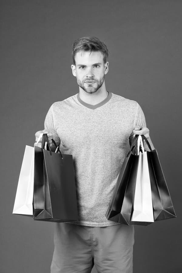 Opportunità di bloccaggio Il fronte barbuto dell'uomo tiene i sacchetti della spesa Vestiti ed accessori sportivi del lotto compr fotografie stock