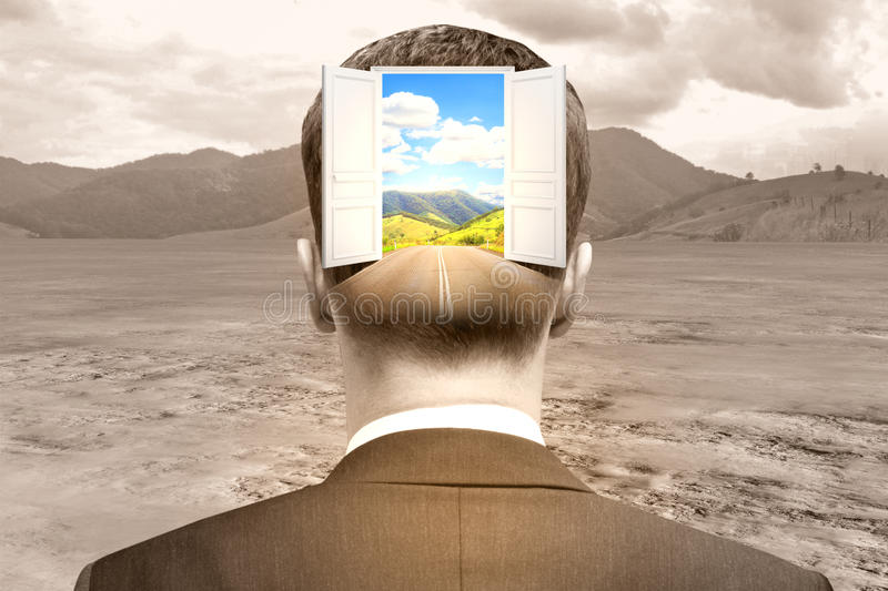 Opportunity concept. Back view of businessman with abstract open door and landscape view in head on desert background. Opportunity concept royalty free stock image