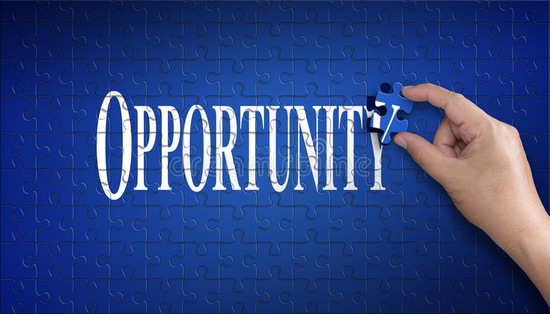 Opportunity word on Jigsaw puzzle. Man hand holding a blue puzzle to complete the word Opportunity divided over them conceptual o stock photo