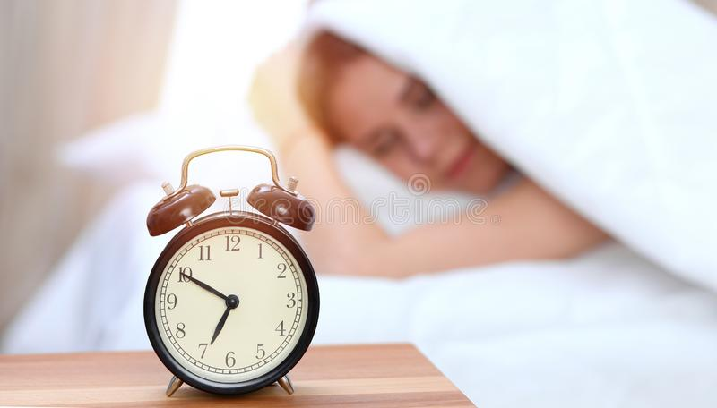 Opposé de réveil de jeune femme somnolente Réveillez-vous tôt, en n'obtenant pas à assez le concept de sommeil image stock