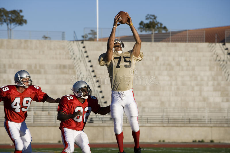 Opposing American football players competing for ball during competitive game, offensive receiver catching ball in mid-air royalty free stock images