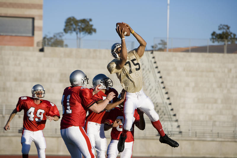 Opposing American football players competing for ball during competitive game, offensive receiver catching ball in mid-air.  stock photo