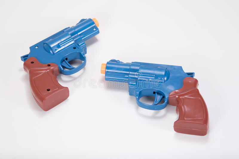 Opposing plastic toy handguns with copy space. Two opposing plastic toy handguns on a plain white background with copy space stock photo