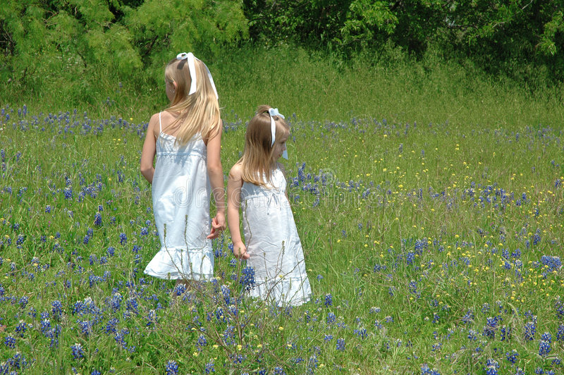 Opposites. Two sister chasing bugs and spending the day in blue bonnet flowers Blue Bonnets are native Texas flowers. The Blue Bonnet is the State Flower royalty free stock image