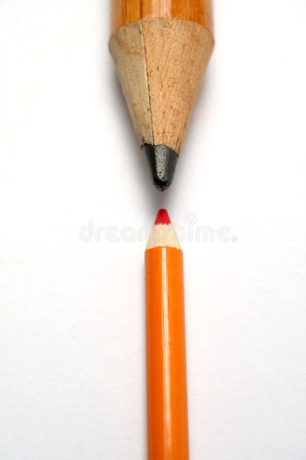 Opposition of a small and greater pencil royalty free stock photography
