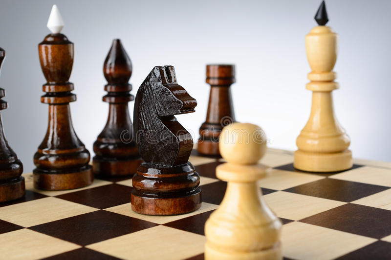 The opposition of white and black chess pieces. On a chessboard royalty free stock photography